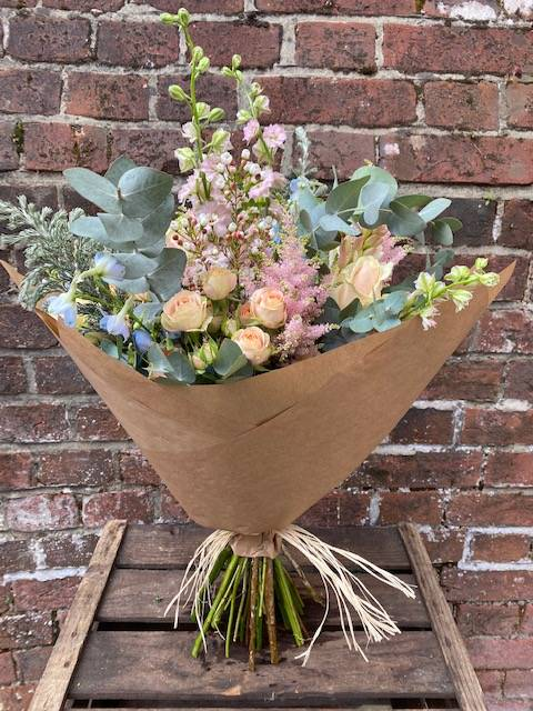 Bouquet with eucalyptus, delphiniums, spray roses, larkspur, wax flower in brown paper